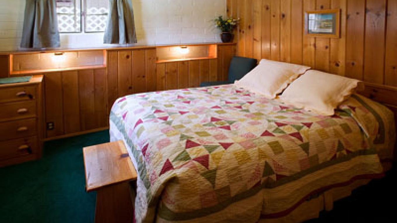 Quilted queen bed in bedroom – Lake Front Cabins