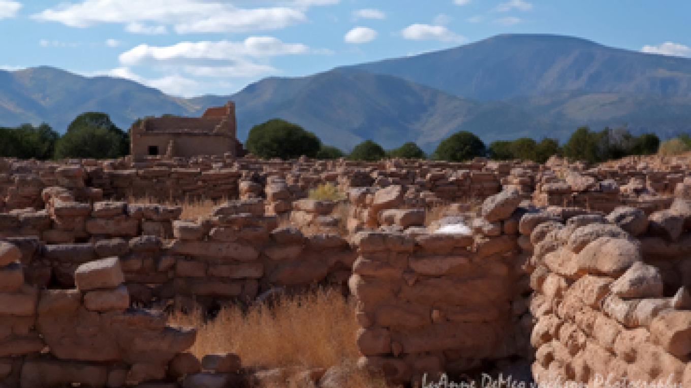 Mesa top village ruins against Jemez Mountains. – Lu Ann Jackson