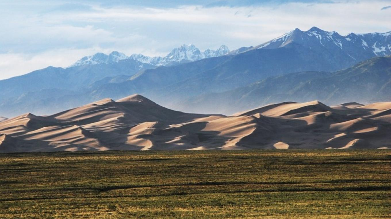 The Sangre de Cristo Mountains rise in dramatic contrast to the Great Sand Dunes. Photo from park entrance in June. – NPS/Patrick Myers