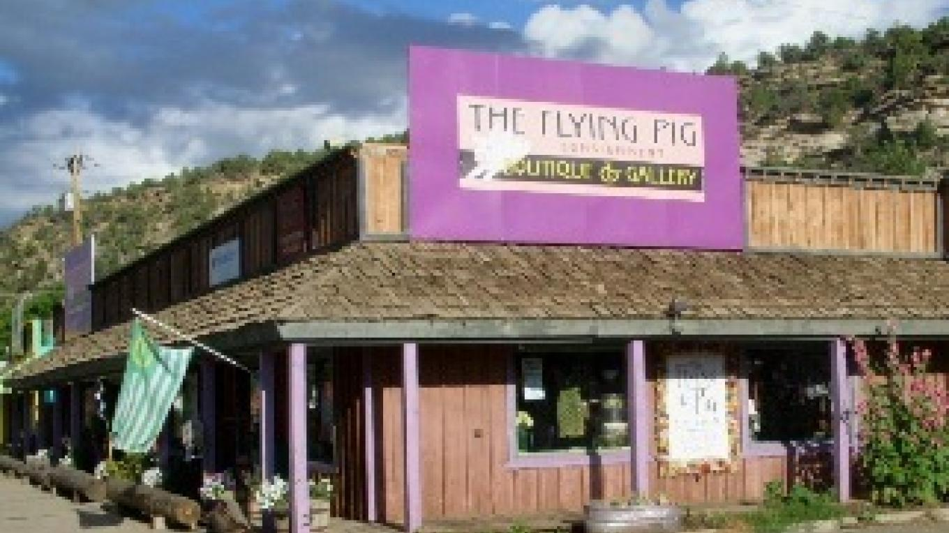 Facing the morning sun, a cheery Flying Pig signage points the way to the unexpected eclectic. – Mary M Sparks