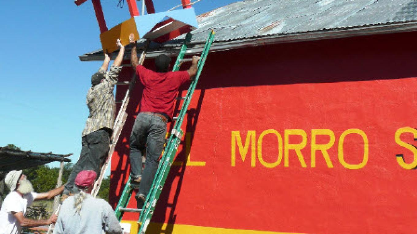 The community rallies for the raising of the bell tower on the newly painted Old School Gallery – EMAAC