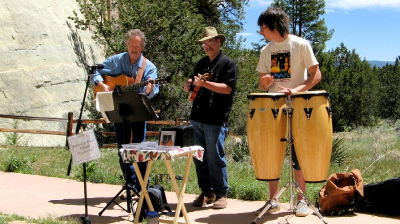 Don Grieser (center) making music with Jonathon Lee Pickens (left)  and Walker Pickens (right)  in front of the ancient pool at El Morro National Monument, during a free Memorial Day concert – Kirk Shoemaker