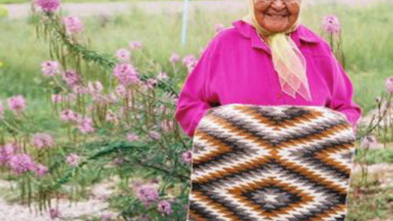 Mary Pino, Navajo Weaver holding one of her beautiful traditionally woven Navajo Rugs. – Pickens
