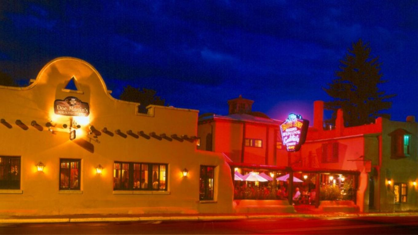 Facade of the Taos Inn at night with our illuminated neon sign. The Oldest neon sign in Taos County. – Jeff Caven