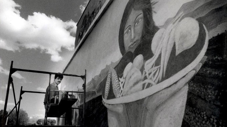 Carlos Sandoval painting mural on north wall of Jacales Gallery – Huberto Maestas