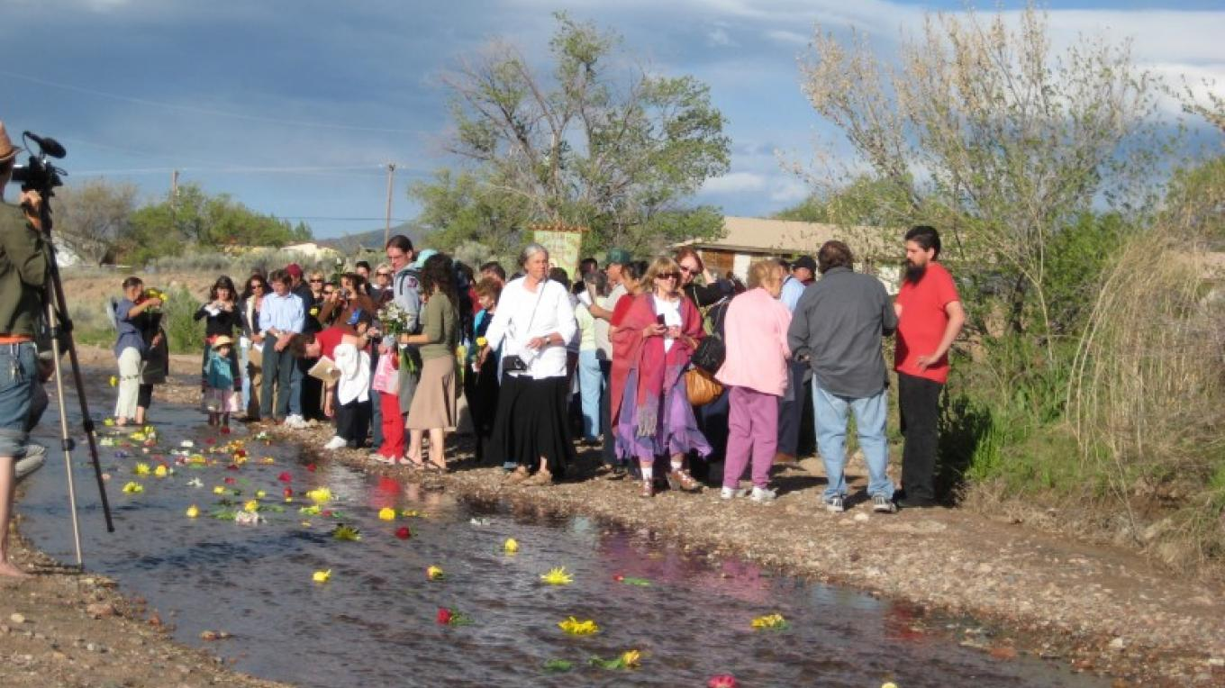 Release of the blessed flowers into the Santa Fe River asking San Isidro for a bountiful year ahead.  A treasured time for children – Letitia Mee
