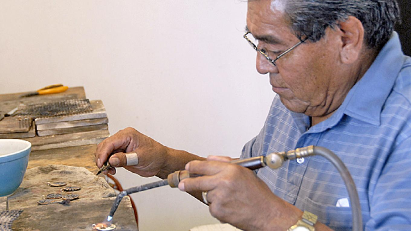 Weaver Salina works on an original design of a piece of sterling jewelry. – lizardlight