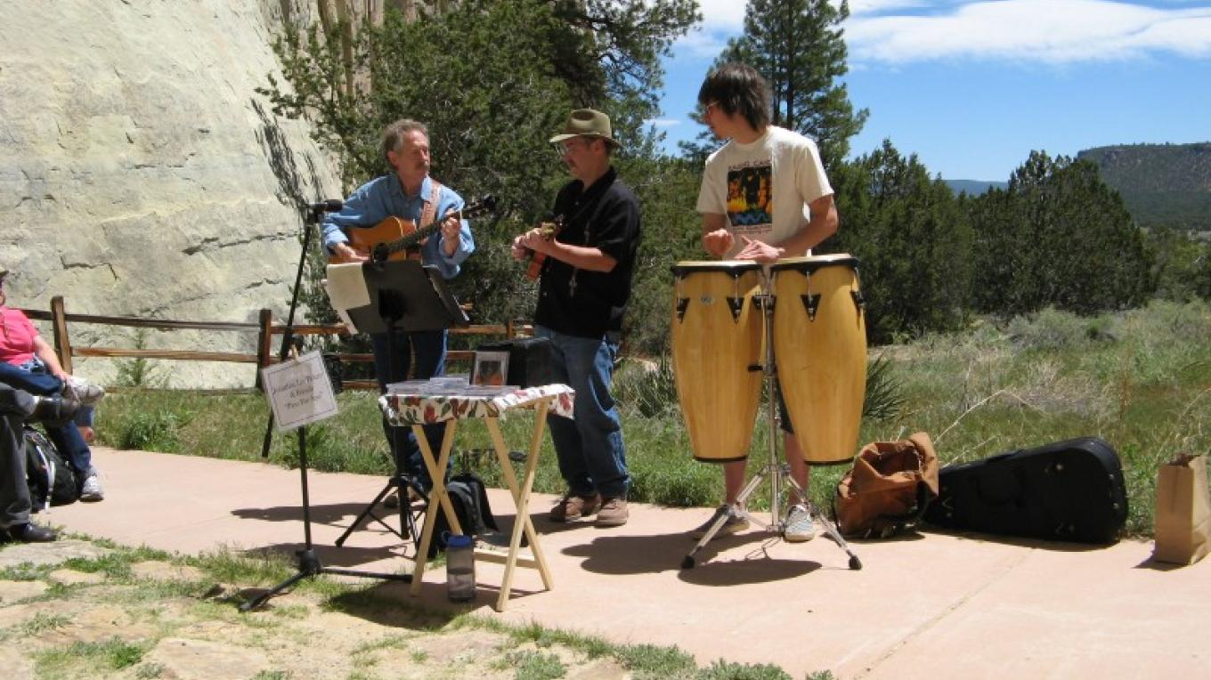 "Jonathan Lee Pickens (left) debuts his new song 'Paso Por Aqui"" in front of the natural oasis pool at El Morro National Monument, with his son Walker on drums and friend Don Grieser on mandolin. – Kirk Shoemaker"
