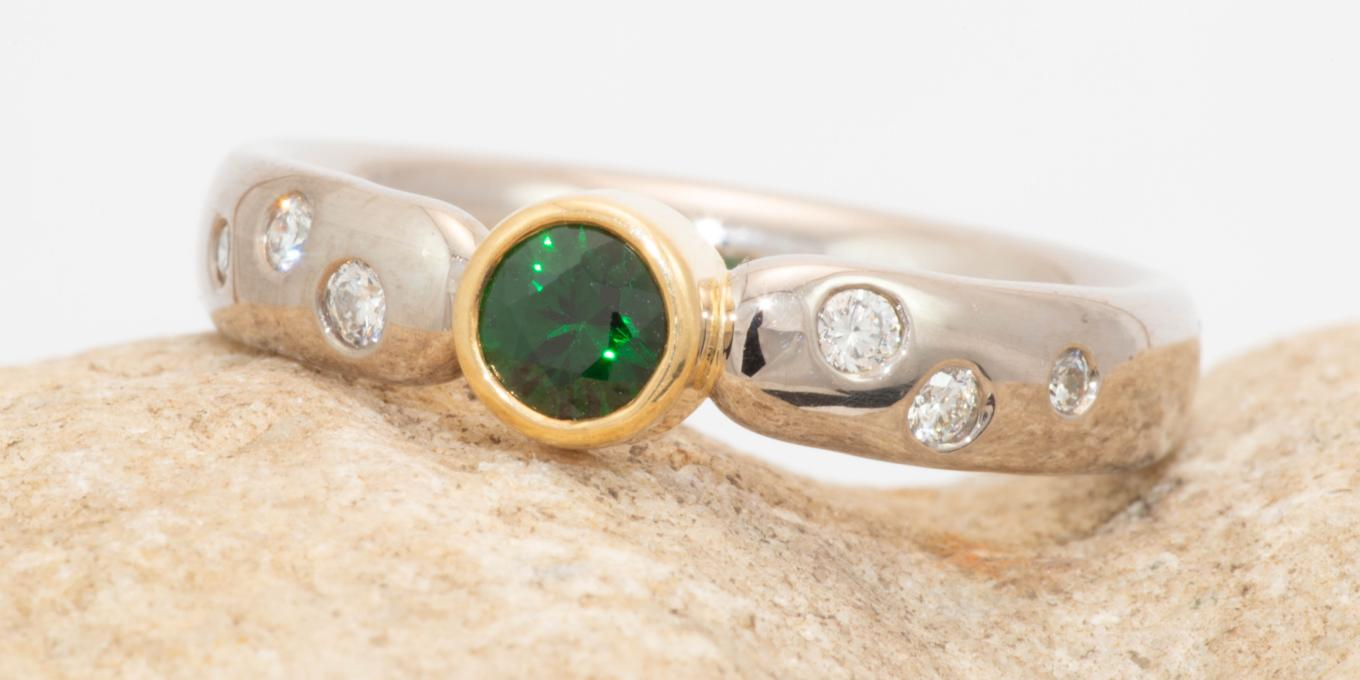 Rare Green Tsavorite Garnet set in 18k yellow and white gold ring accented with 6 gypsy set diamonds. $4000.00 – Reminiscent of the dark green foliage of Waterton Park this Tsavorite Garnet ring will be a beautiful reminder of your visit to Waterton for years to come.
