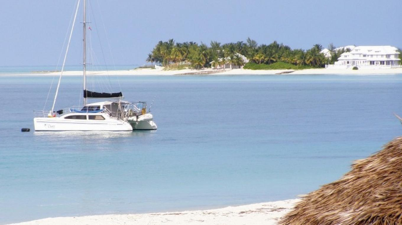 A small boat sailing on the Treasure Cay Beach. – Rhonda