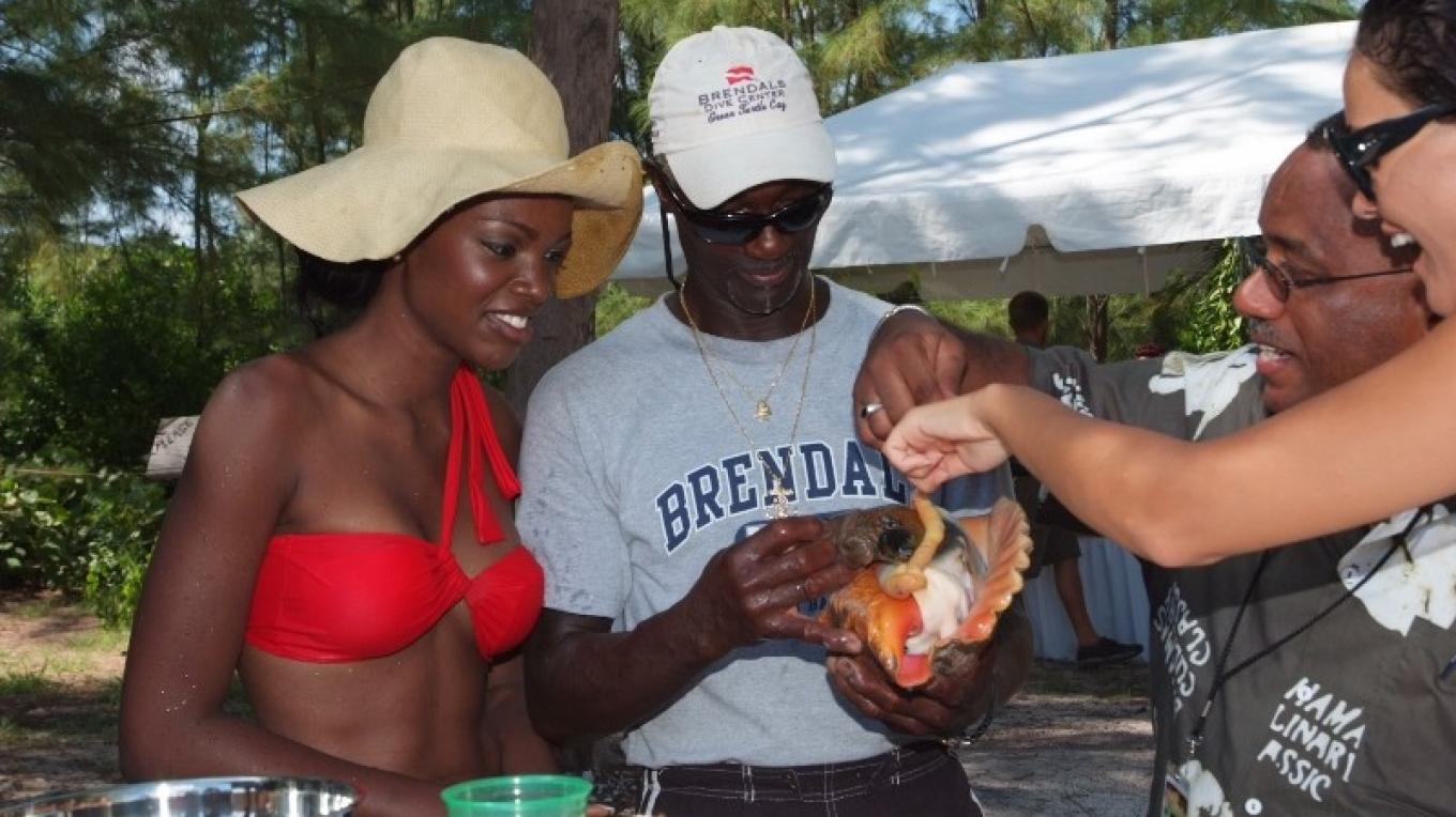 Tourist examines a conch. – Brendal's Dive Center