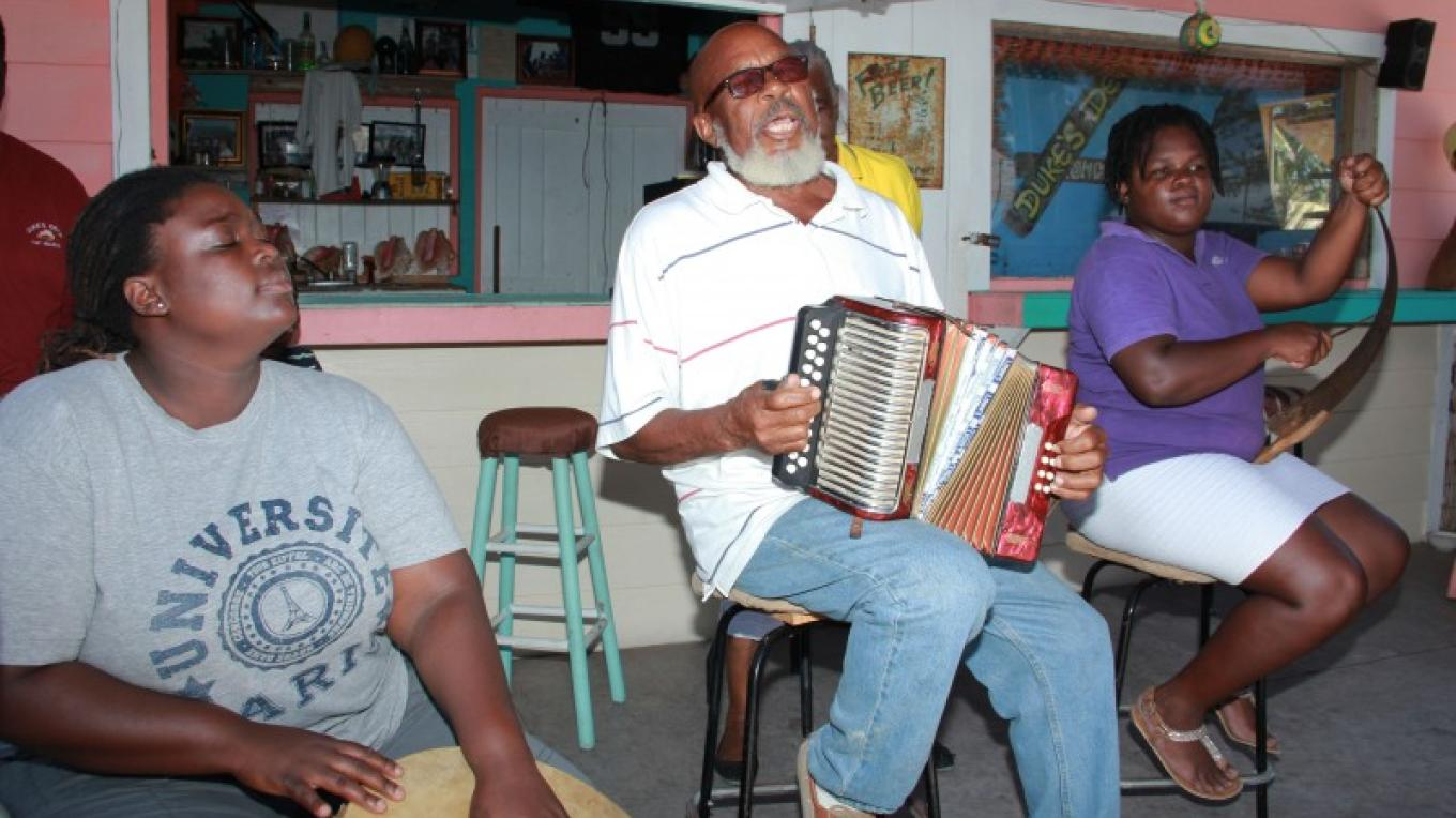 "Cedelle Hunter beats the goatskin drum, Pompey ""Bohog"" Johnson plays the accordion, and Crystal Smith bends/scrapes the saw, alternating between different musical tones. – Bahamas Ministry of Tourism"