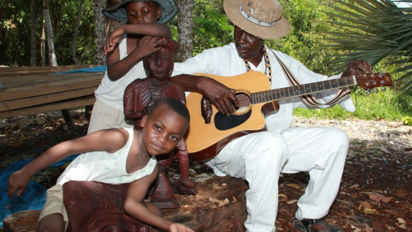 Man playing guitar and children of Red Bays. – Ministry of Tourism