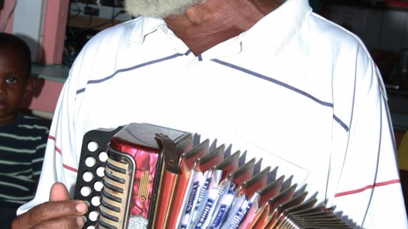 "Veteran Rake & Scrape artist, Pompey ""Bohog"" Johnson, belts out a smooth set of lyrics, as he maneuvers his accordion. – Bahamas Ministry of Tourism"