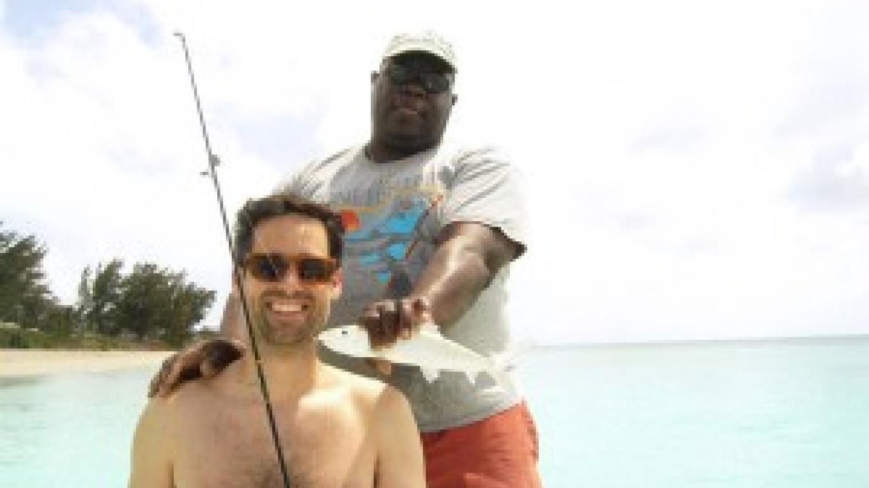 Bonefish Ebbie holding a bonefish that the tourist caught – Bimini Bonefish Club