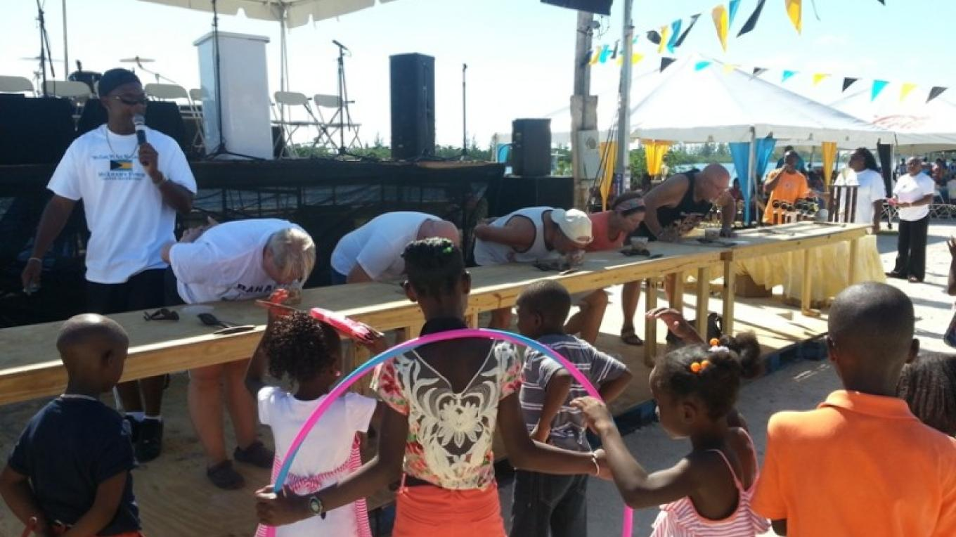 "Visitors participate in the ""Conch Eating Contest"" at the McLean's Town Festival. They cannot use their hands to eat the conch salad. – Bahamas Ministry of Tourism"