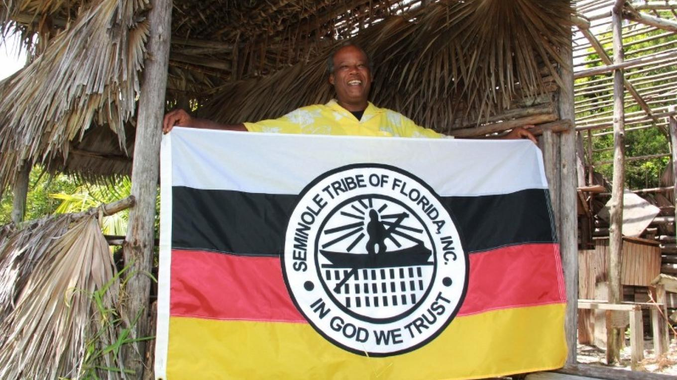 Androsian Peter Douglas holding the Flag of the Seminole Tribe of Florida, Inc.. It was donated by the tribe to the village. – Ministry of Tourism
