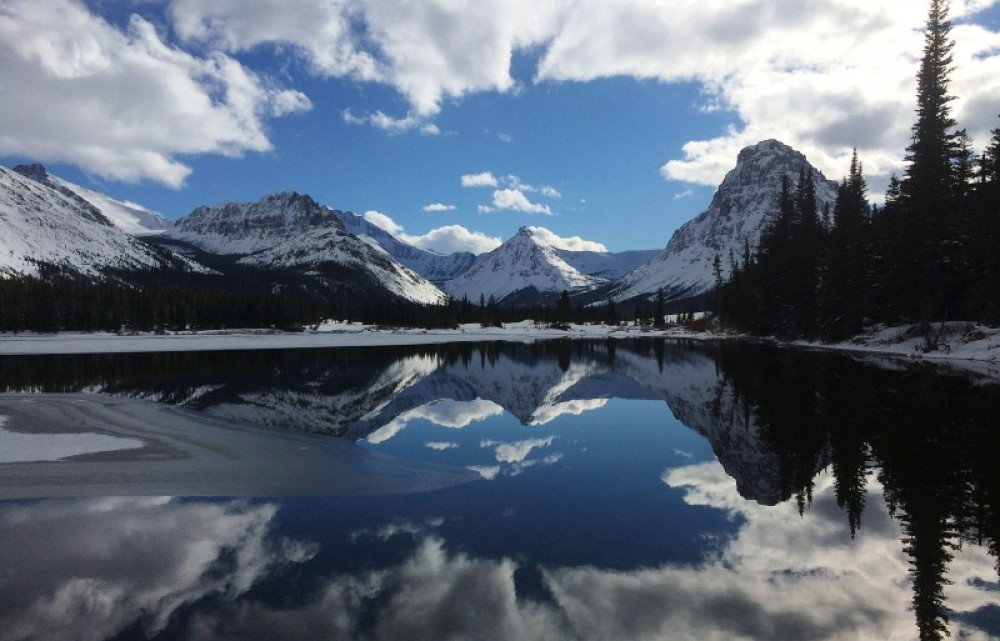 Reflections on the water of Upper Two Medicine Lake. – Devin Schmit