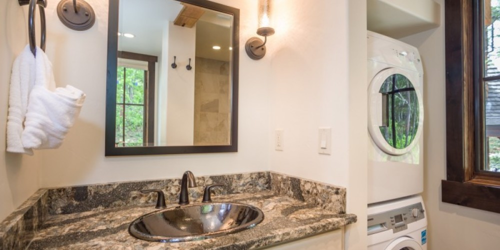 The main level full bath, with a shower, washer and dryer, serves as the master bath as well as the powder room. – Trevon Baker
