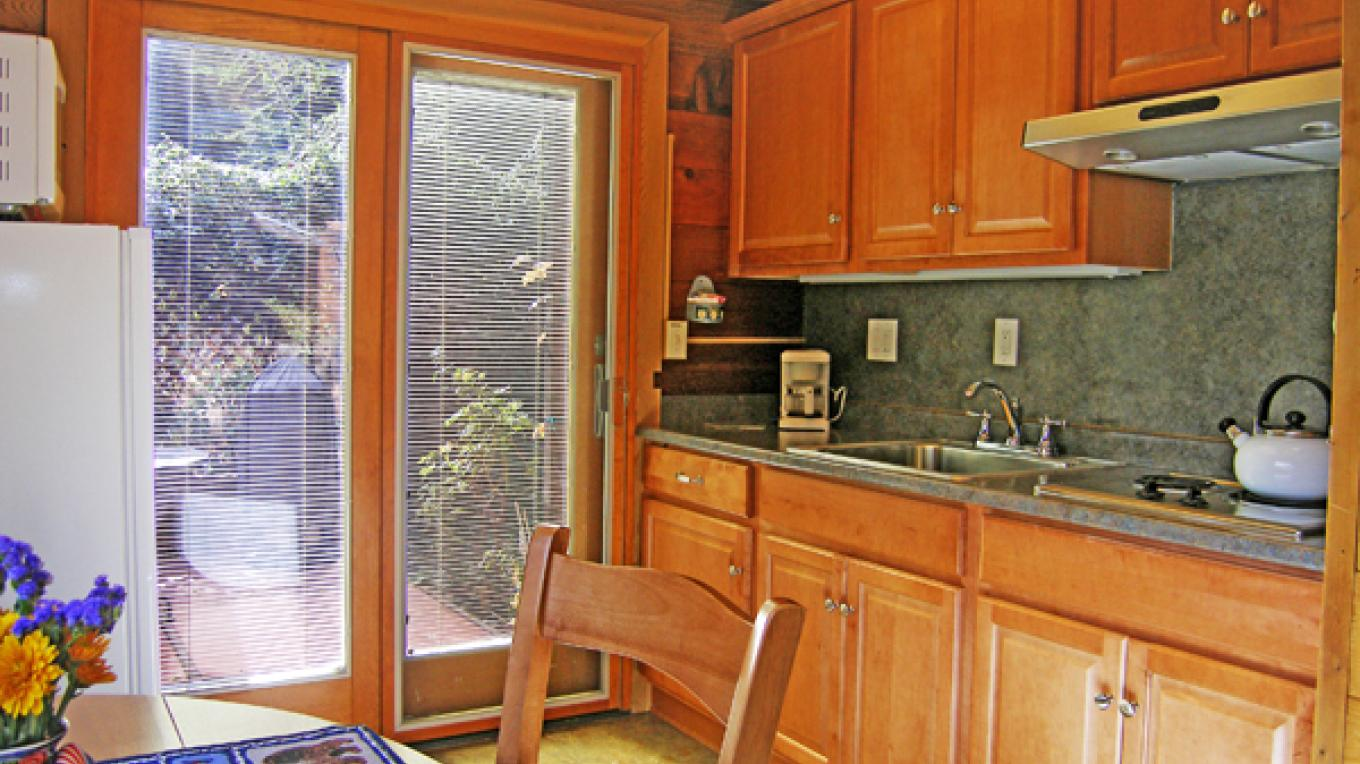 Comfortable chalet cabin kitchen with door to the private patio. – Sedona Sky