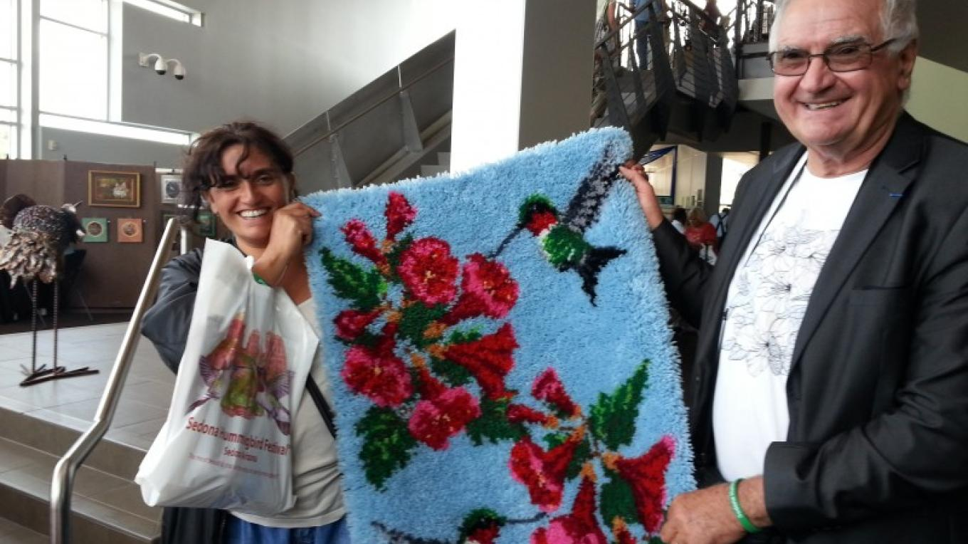 Dr. Jacques Ducros and daughter Alexandra from Pont de L'Etoile, France, display the hand-crocheted rug they won at a raffle at the 2014 Festival – Beth Kingsley Hawkins