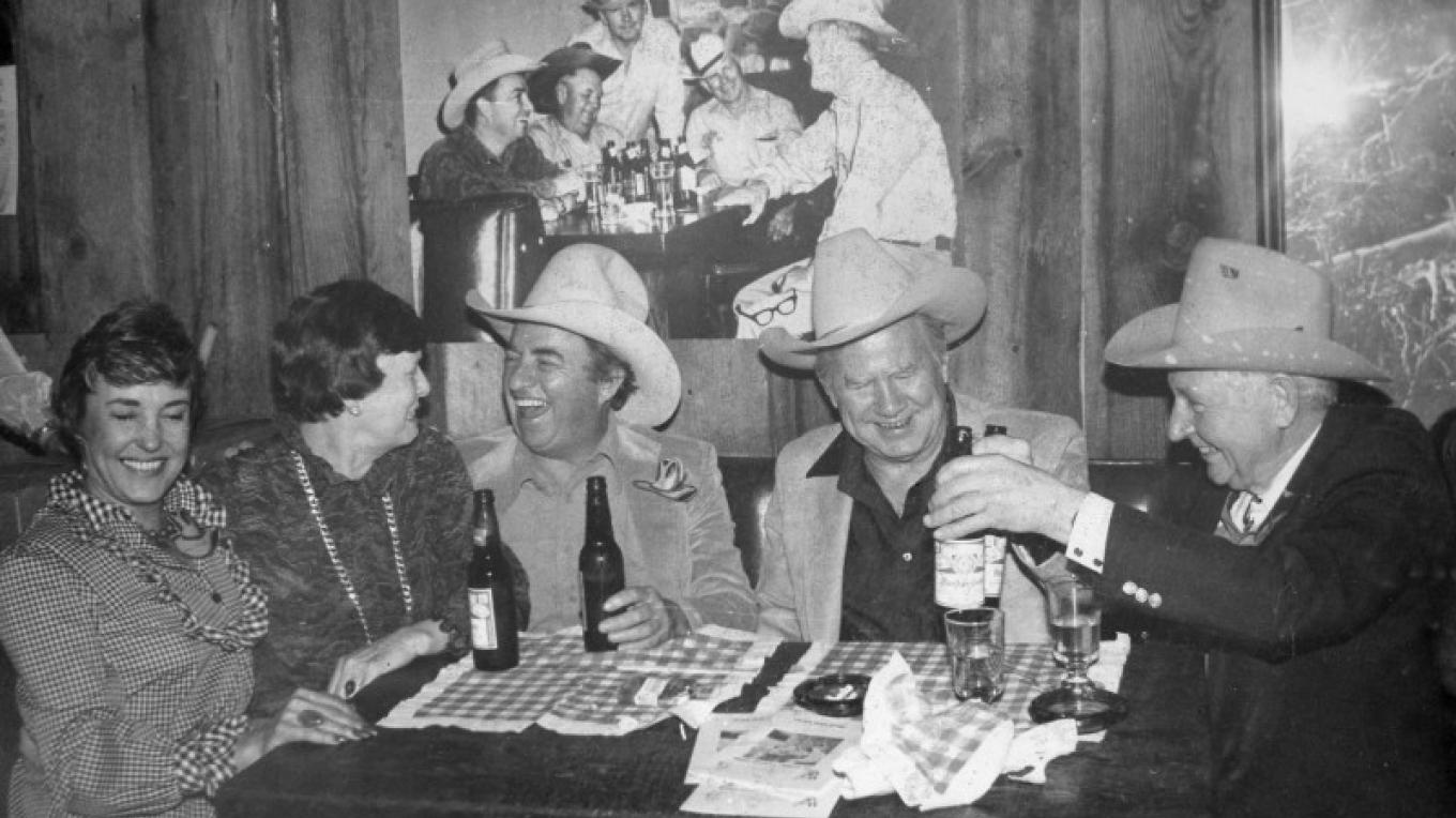 CAA members and friends celebrate the founding of the organization in the Oak Creek Tavern under a photo taken in 1965. – Elizabeth Rigby, Courtesy Sedona Heritage Museum