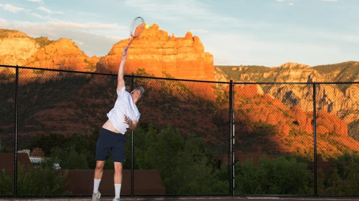 Player hitting a serve with the beautiful geological rock formations of Sedona in the backgroud. Getting fit and having fun. – Matt Valley