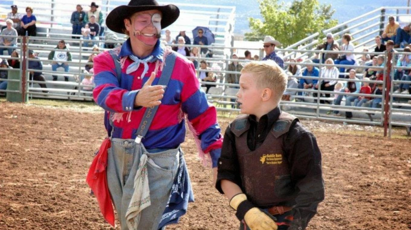 Fort Verde Days rodeo clown getting ready to high-five a successful little calf rider. – Town of Camp Verde