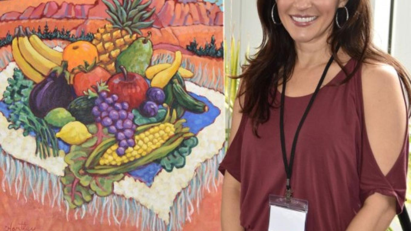 """Sedona is a city """"animated by the arts,"""" and VegFest features artistic expression. Here, Julieanna Hever admires the official VegFest 2017 theme painting, """"Plant Yourself in the Red Rocks,"""" by Claudia Hartley. – Don Fries"""