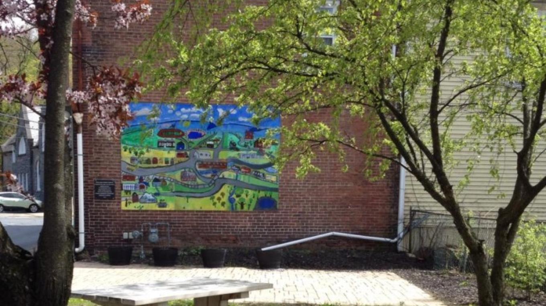 "Main Street pocket park in spring. ""Our Town"" heritage mural. On N. Main Street between Broadway and Market Sts. – Sharon J. Davis, Slate Belt Community Partnership"