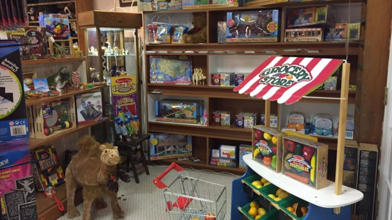 Corner of Orion's Toyworks containing boxed train sections, Farmers Stand with shopping cart, and more musical instruments. – Theresa Veltri
