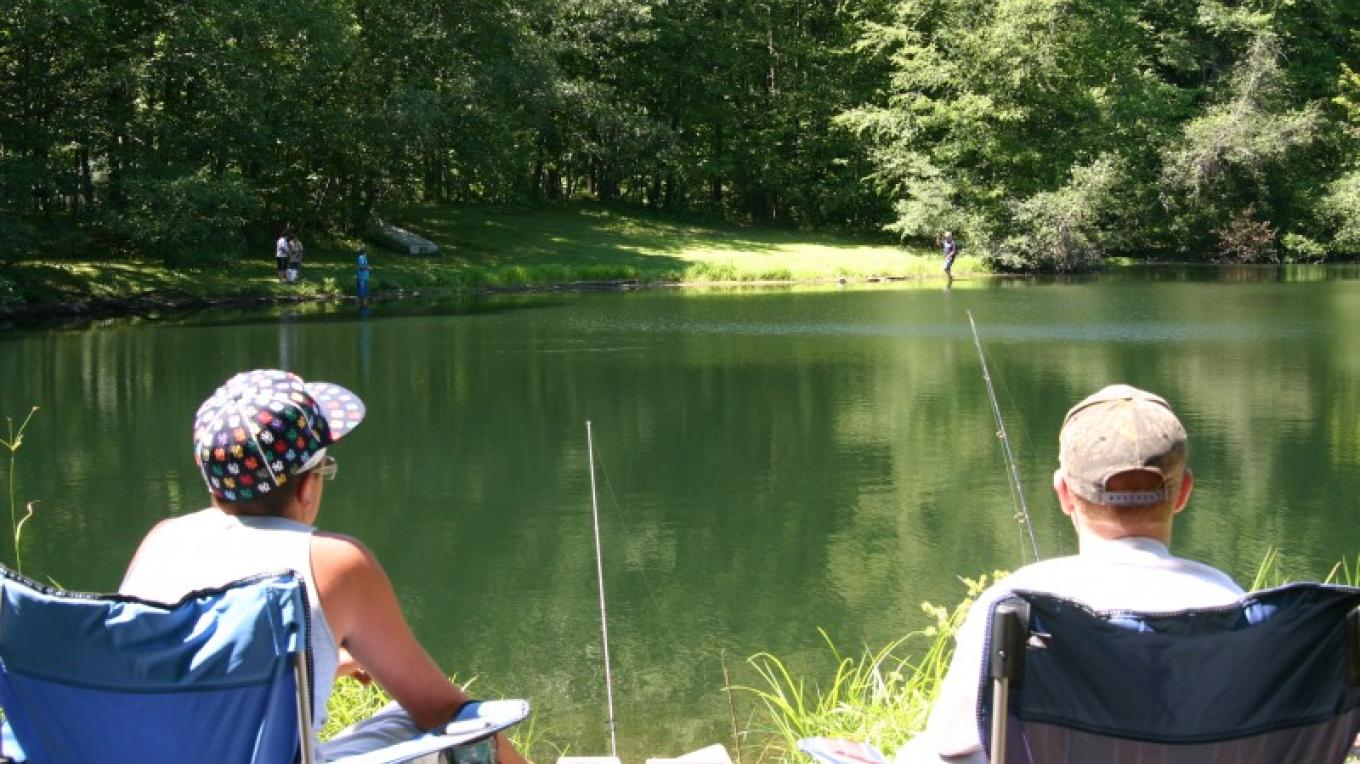 Relaxing in the sunshine fishing in our stocked lake. – Photograph by: Kymer's Camping Resort