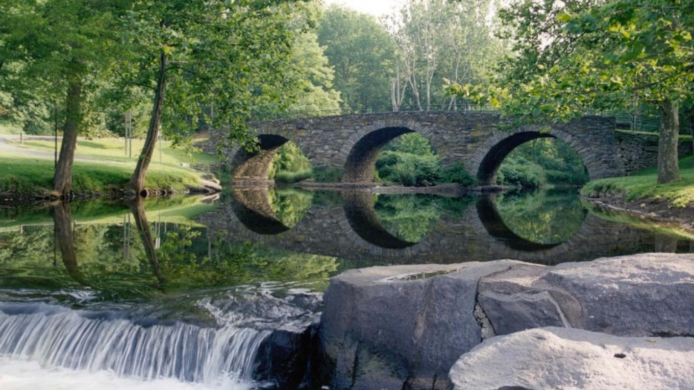 Stone Arch Bridge with reflecting pool and waterfall – Photo by: Sullivan County Parks