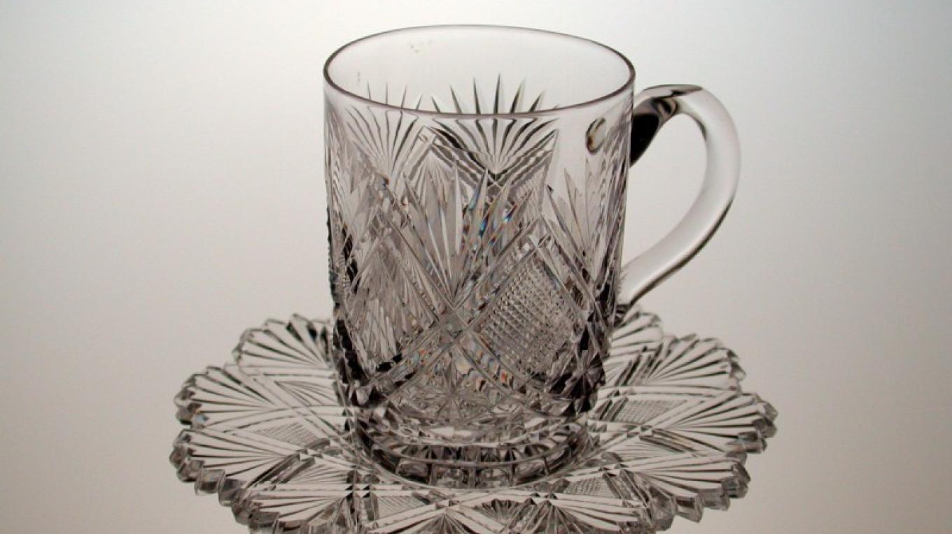 A colorless glass punch cup with matching under plate, cut in the Parisian pattern by C. Dorflinger & Sons. The Parisian pattern was designed by John S. O'Connor in 1886. – Henry J. Loftus