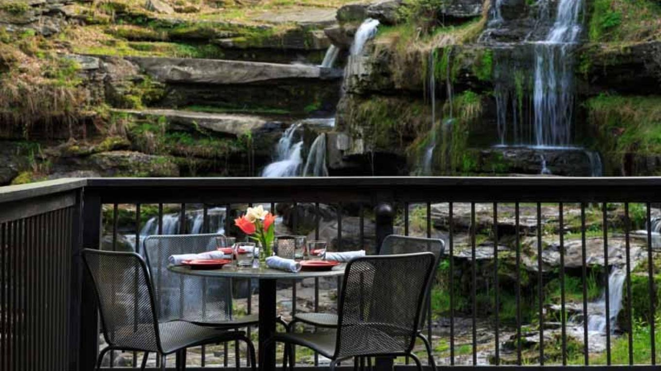 "Enjoy stunning views of the river gorge falls in the panoramic dining room and decks at ""Glass."" – Jumping Rocks"