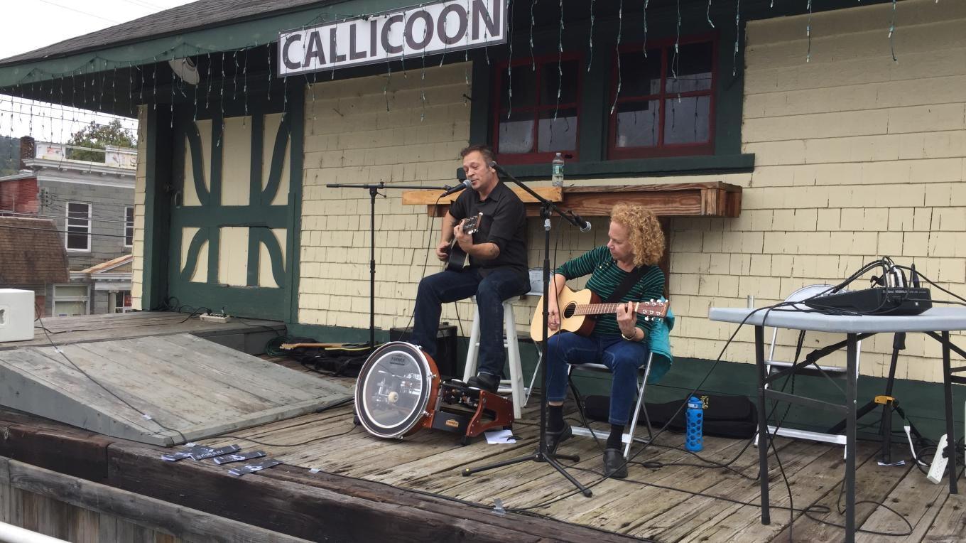 Central New York Railroad has graciously allowed use of the Callicoon Depot's former loading dock as a stage for popular community events. Above, musicians Brewster Smith and Elizabeth Rose perform. – Photo by Evan Eisenberg