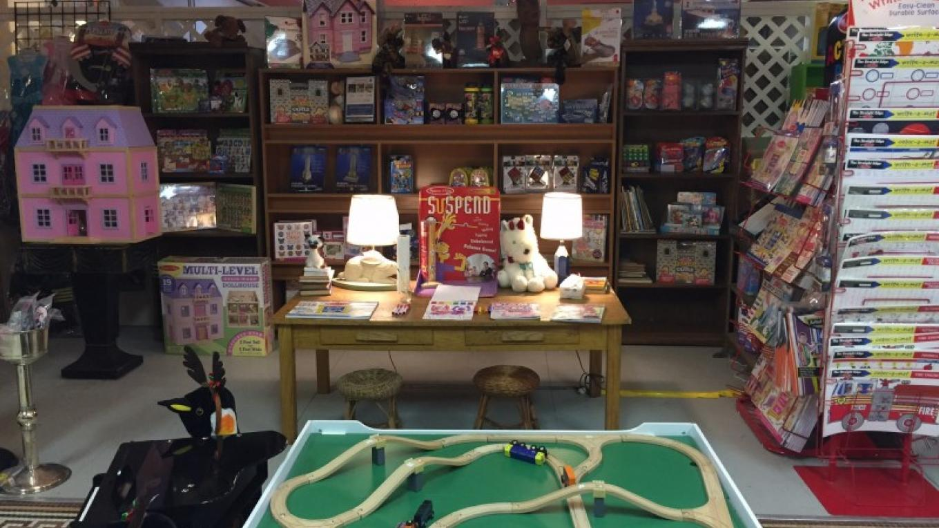 View of the left side of Orion's Toyworks showing the children's craft table and train table. – Theresa Veltri