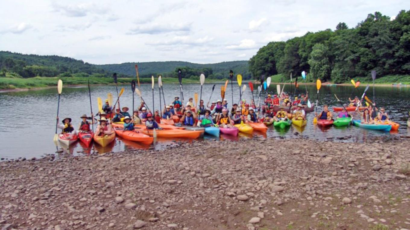 Sojourners hold their paddles high to celebrate completing the first day of the 2012 Delaware River Sojourn at the takeout in Milanville, Pa. – Dejay Branch, National Canoe Safety Patrol