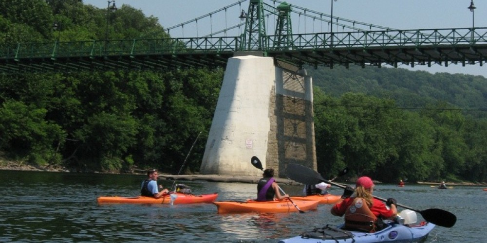 Sojourners paddle under the Bulls Island-Raven Rock Footbridge in the non-tidal Lower Delaware River, a section of the Delaware that is a nationally-designated Partnership Wild and Scenic River. – Delaware Canal State Park