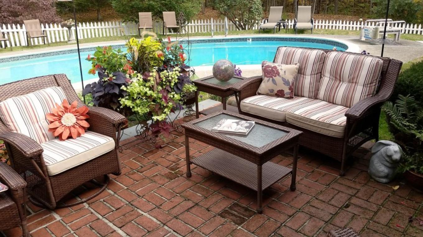 Relax on the patio next to the in-ground pool. – Wooden Duck B&B