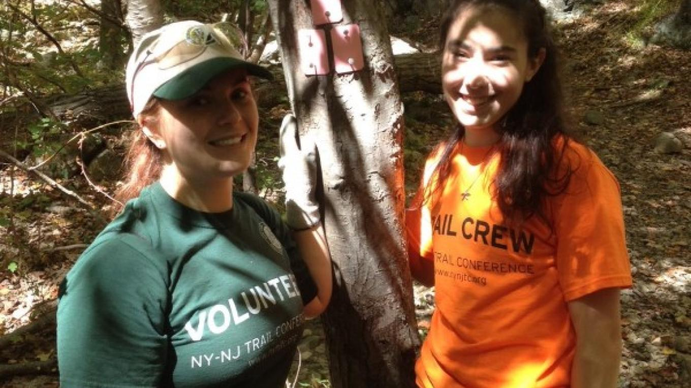 Two college-age volunteers add tag blazes to a new trail. – Peter Dolan