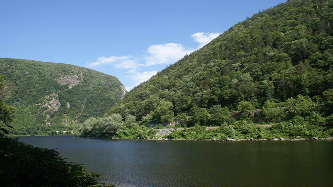 The Delaware River flows through a gap between Mt. Tammany in New Jersey and Mt. Minsi in Pennsylvania. Both of these mountains provide iconic views, accessible from strenuous hiking trails. – National Park Service