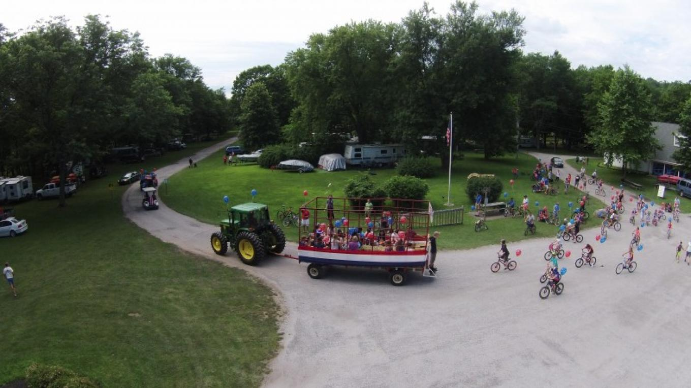 Campers enjoying a hayride around the campground, this hayride in celebration of the 4th of July. – Photograph by: Driftstone Campground