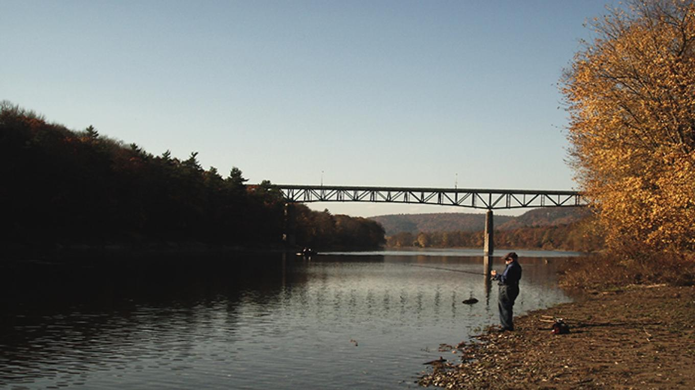 A lone fisherman enjoying the Milford Beach Access. Downstream is a view of the Rt 206 bridge into New Jersey. – National Park Service