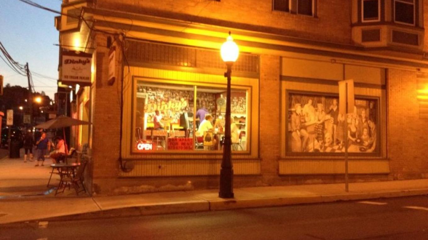 """Dinky's Ice Cream shop illuminated on a Saturday night. Also featuring the """"Soda Shop"""" heritage mural. At 1st and Broadway, Bangor. – Sharon J. Davis, Slate Belt Community Partnership"""