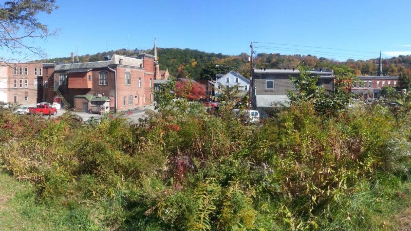 View from Commercial Street in Honesdale, looking east and out over the railroad tracks and onto downtown. Borough hall, church steeples, and Irving Cliff fill the horizon. – Derek F. Williams