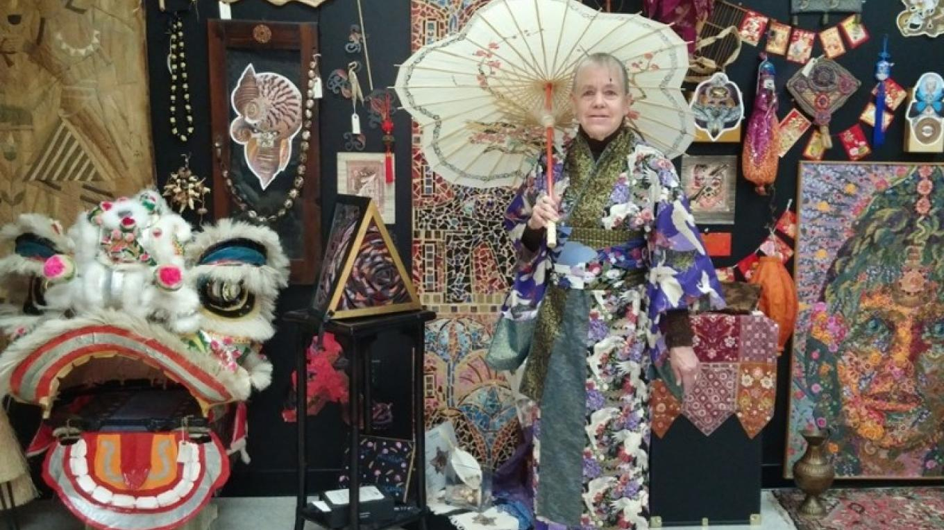 Performance artist Marya, in a kimono of her own creation, poses in front of her museum's floor to ceiling cultural outpourings. – Lester Morrow