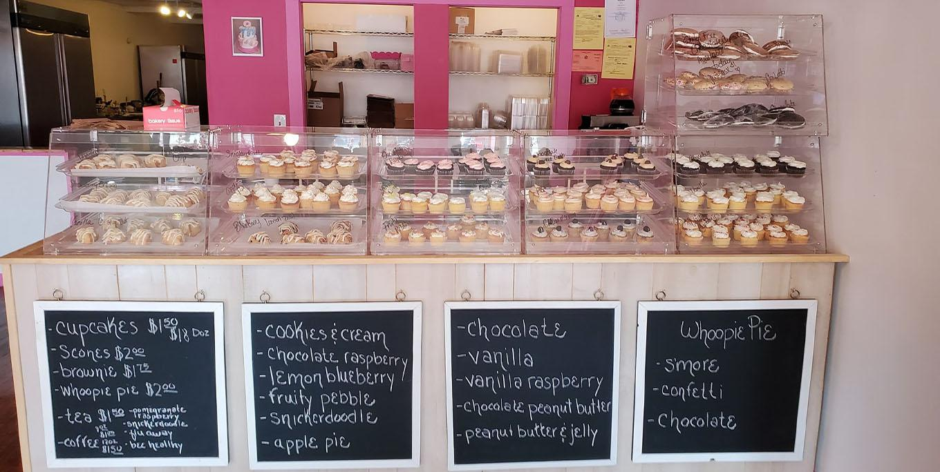 Inside of For the Love of Flour, showing cupcakes, cookies, and a chalkboard menu.