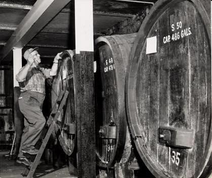 Leo Goering checking on the wine barrels at O-Neh-Da circa 1945.