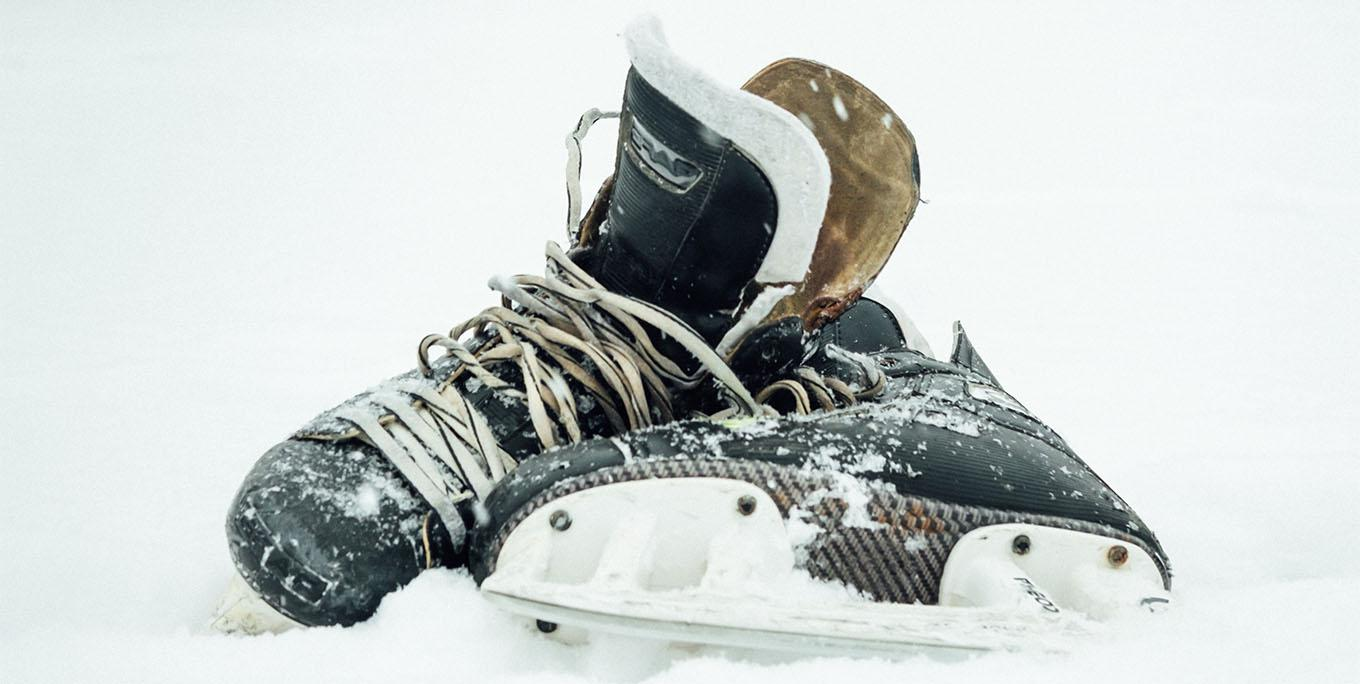 Close-up shot of hockey skates in the snow.